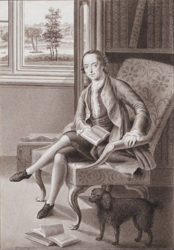 Walpole sitting in chair with bookcases behind and small dog next to him